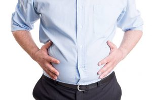 Fullness. Hands grabbing bloated abdomen. Digestion problem or indigestion, medical concept.
