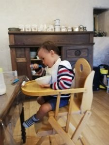 baby holding bowl and eating