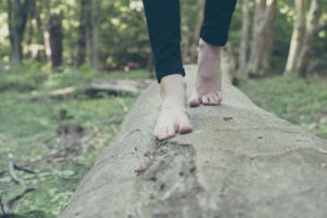 womans' barefeet walking on log