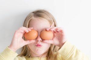 girl holding eggs to eyes